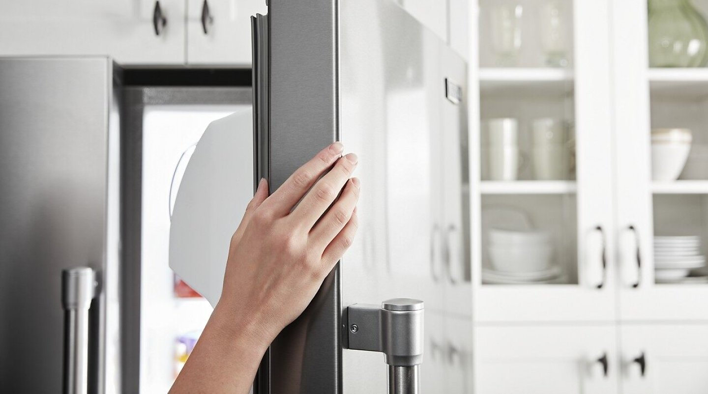 A person opens the door of a Maytag® counter-depth refrigerator.