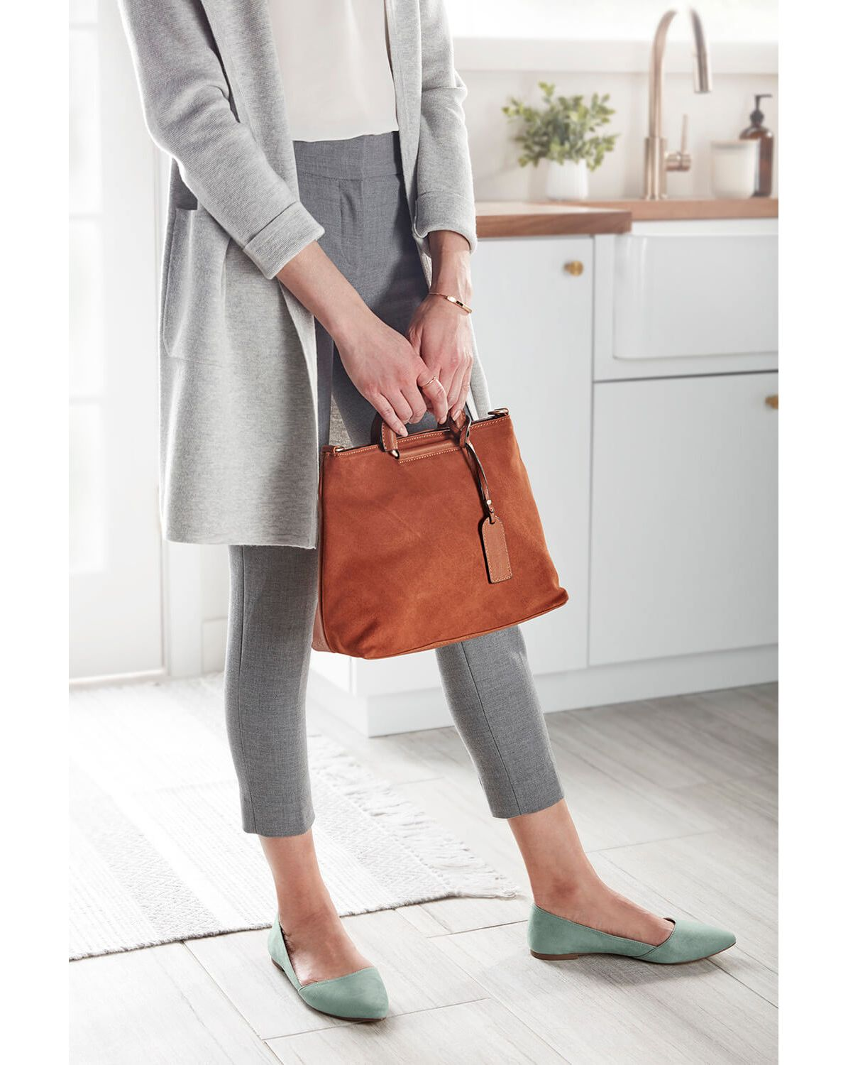 A woman dressed in gray pants, holding an orange purse in her hands, standing in her kitchen