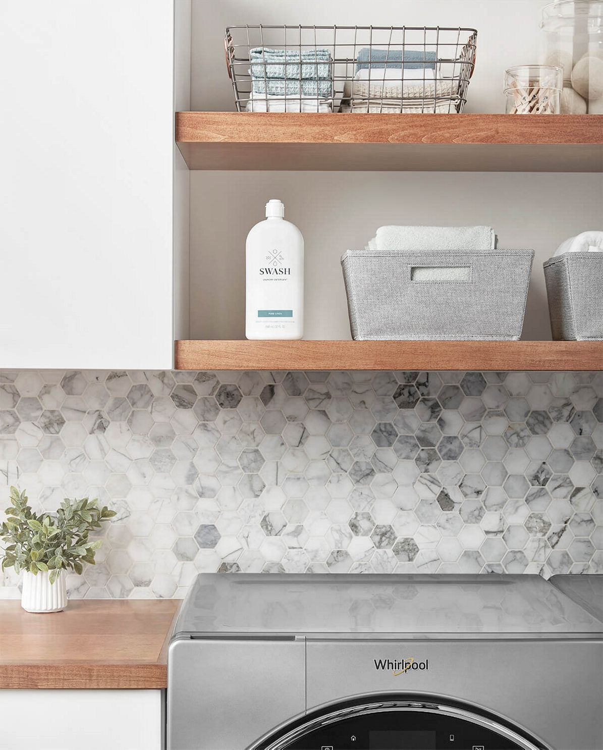 A bottle of Swash Pure Linen Laundry Detergent sitting on an open wooden shelf in a laundry room