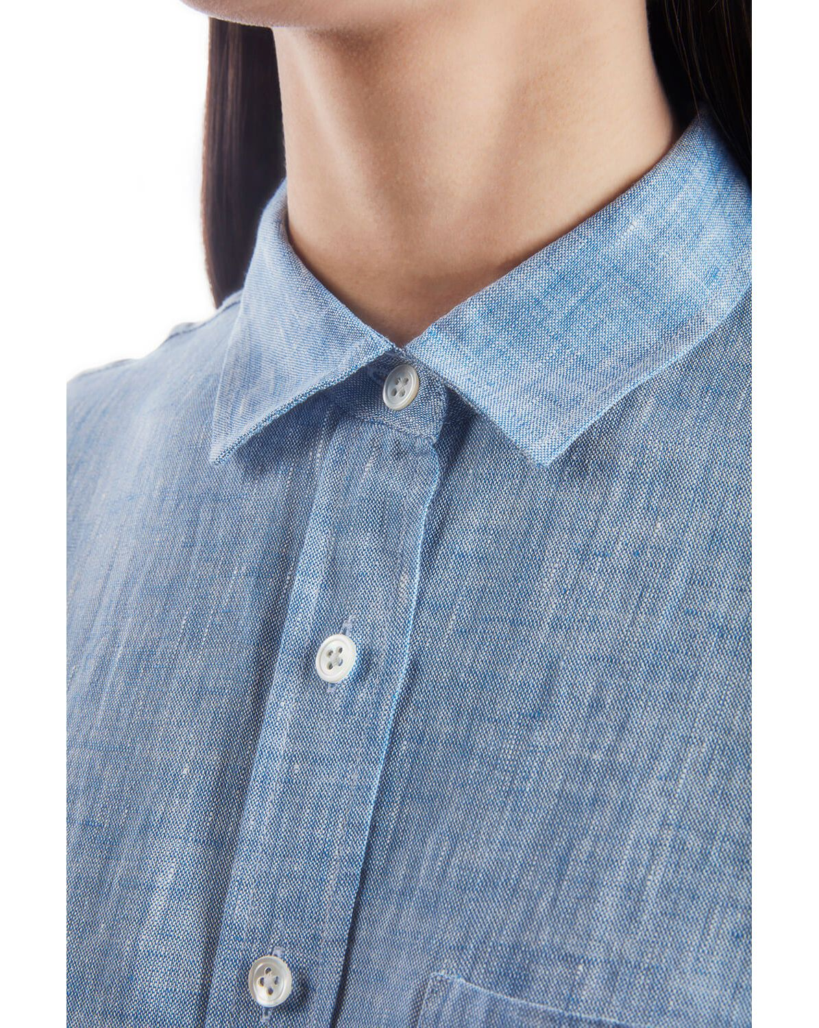 A woman wearing a chambray button down shirt