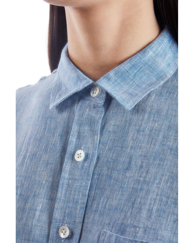 A woman wearing a chambray button down shirt
