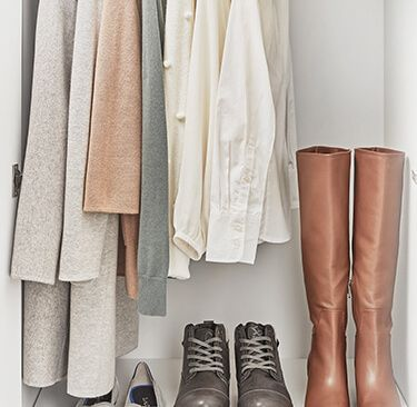 A closet with some hanging clothes and shoes
