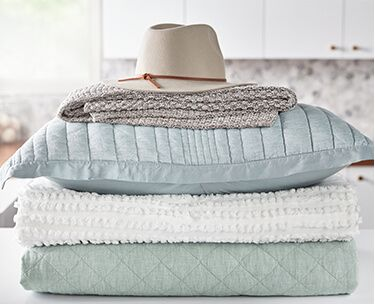 A cream colored sun hat on a stack of freshly cleaned blue linens