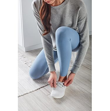 A Woman wearing jeans bending over to tie her white sneaker