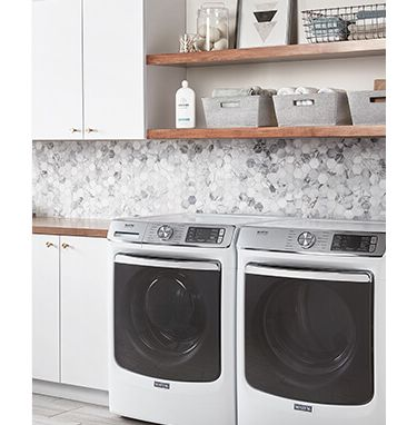 A light and airy laundry room with front loading machines and open shelving