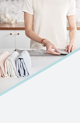 Woman folding laundry on a white countertop