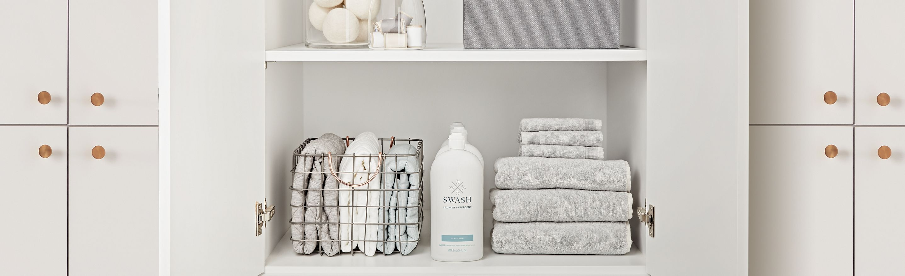 Swash Pure Linen Laundry Detergent on a white shelf in a laundry room next to light gray towels