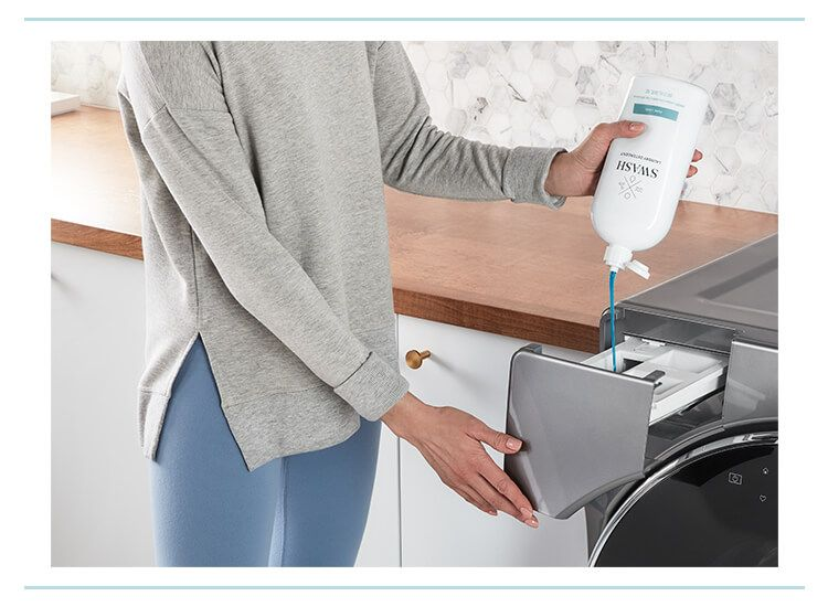 Woman in a gray sweatshirt dispensing Swash laundry detergent using the Precision Pour Cap into a Whirlpool washing machine