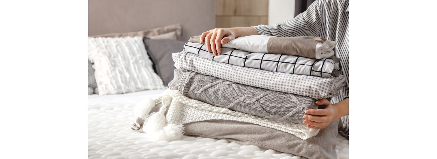 A person holds a stack of fitted sheets and blankets on top of a bed.