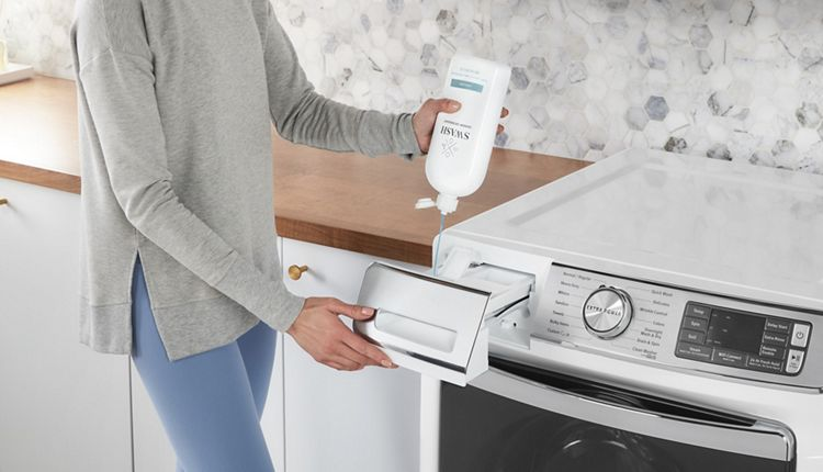 A person pours Swash detergent into the dispenser of a front load washing machine.
