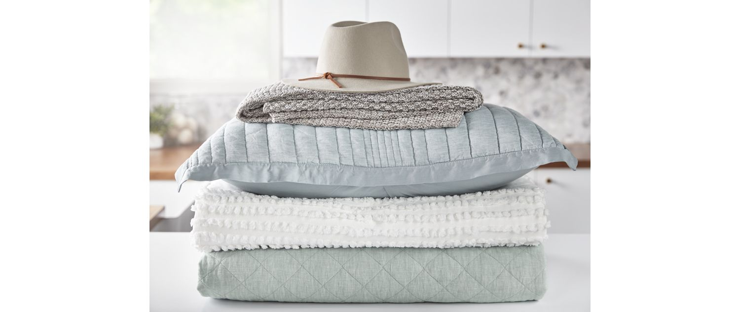 A stack of blankets and pillows with a hat on top sits on a laundry room counter.