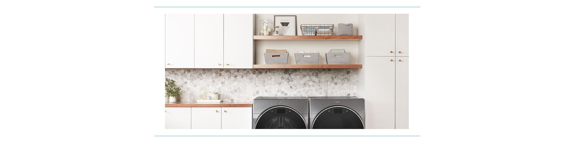 A neatly organized laundry room with open shelves, white cabinets, and Whirlpool front loading washer and dryer