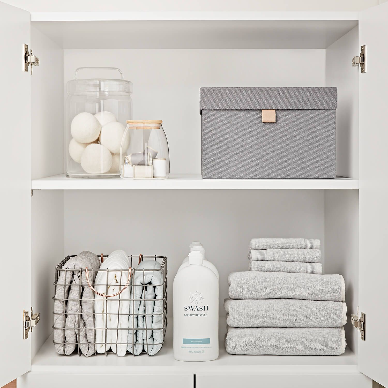 A neatly organized cabinet inside of a laundry room with fresh linens and Swash laundry detergent.