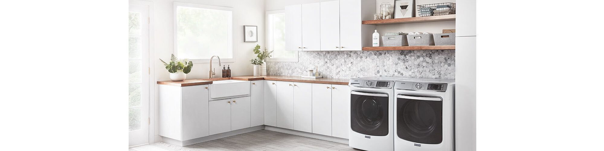 A large laundry room with white cabinets, farmhouse sink, and open shelving with neutral organizational baskets
