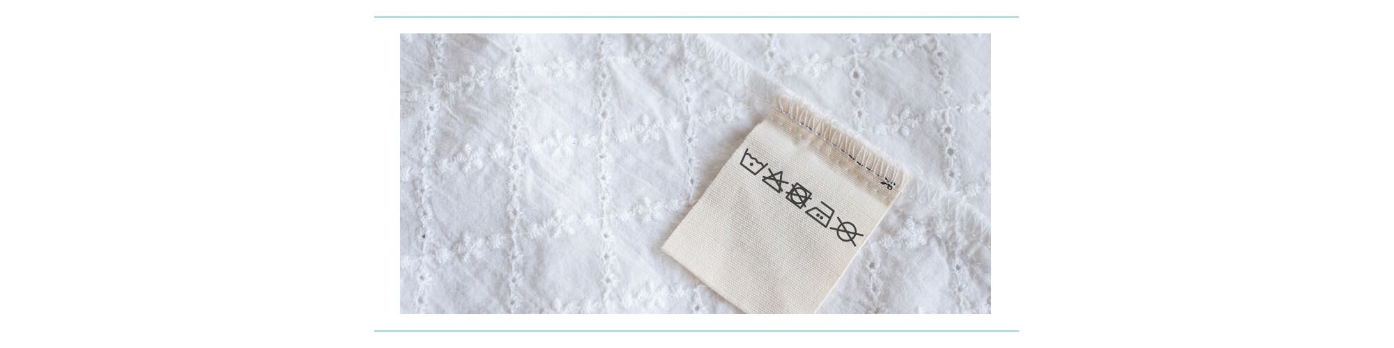 A laundry care tag with symbols on it sewn into a white eyelet piece of fabric
