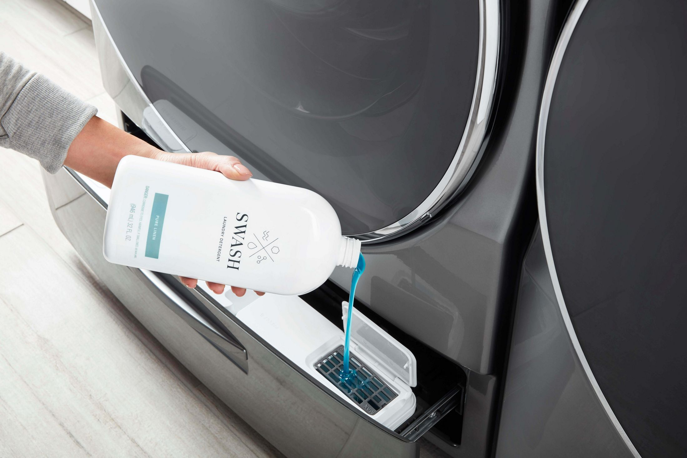 Woman dispensing Swash Pure Linen laundry detergent into her bulk dispensing washing machine