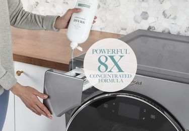 A woman in a gray sweater dispensing Swash laundry detergent into a Whirlpool washing machine dispenser drawer.
