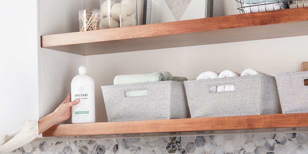 A hand placing the sleek Swash Pure Linen laundry detergent back on a wooden shelf