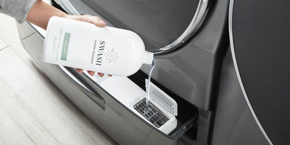 Woman dispensing Swash Pure Linen laundry detergent into her bulk dispensing washing machine