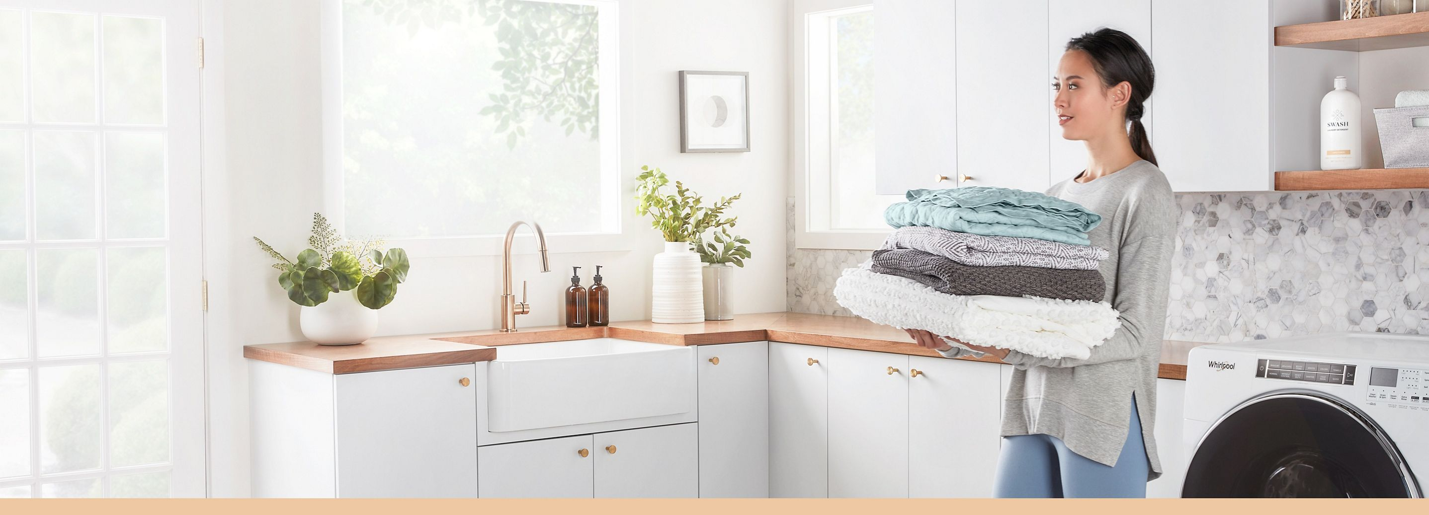 Woman in her laundry room carrying a pile of clean folded laundry