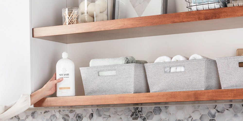 A hand placing the sleek Swash Simply Sunrise laundry detergent back on a wooden shelf