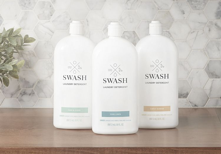 Swash Pure Linen, Free and Clear, and Simply Sunrise Laundry Detergent in sleek white bottles on a wooden surface