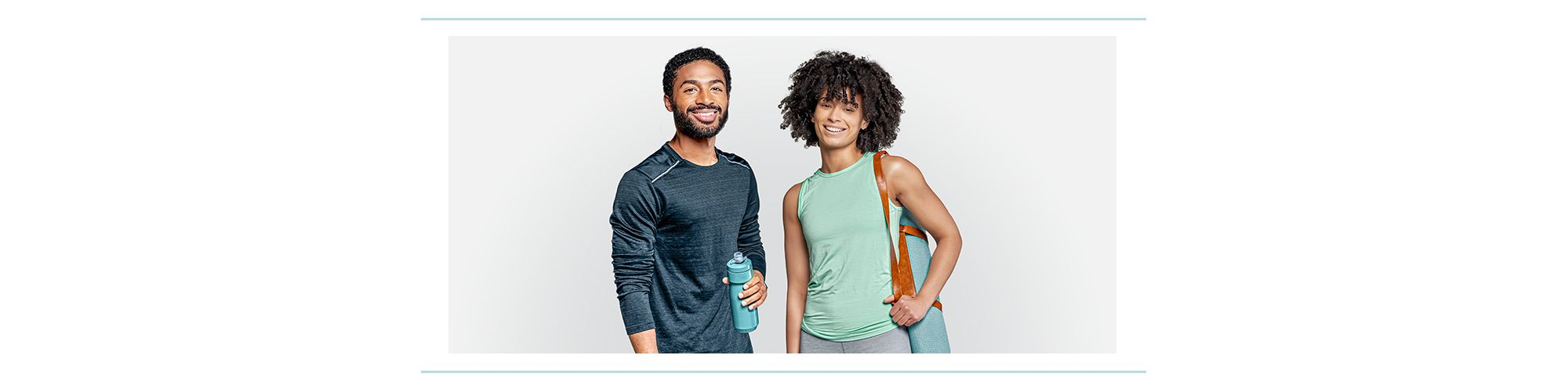 Two people wearing workout clothes and carrying workout gear.