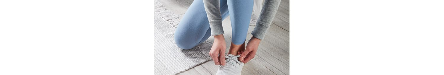 A close-up of someone tying their athletic shoe.