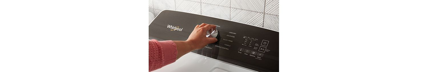 A person adjusts the dial on a Whirlpool dryer.