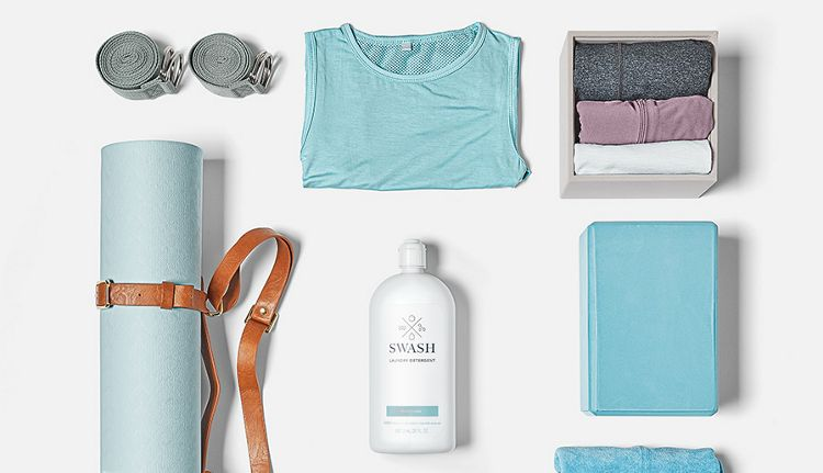 Sets of folded workout clothes and workout gear surround a bottle of Swash laundry detergent.