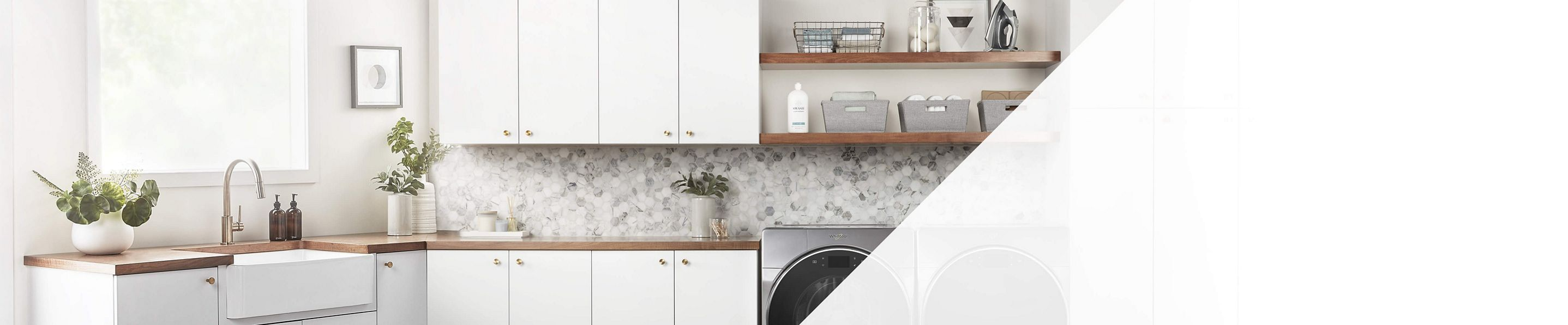A large laundry room with white cabinets and wooden shelves with silver front loading washer and dryer