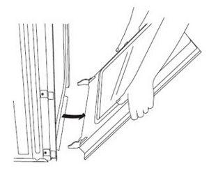 En utilisant les deux mains, attrapez les bords de la porte du four.