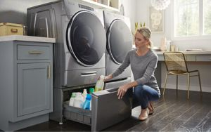 A woman putting away cleaning supplies in a laundry pedestal