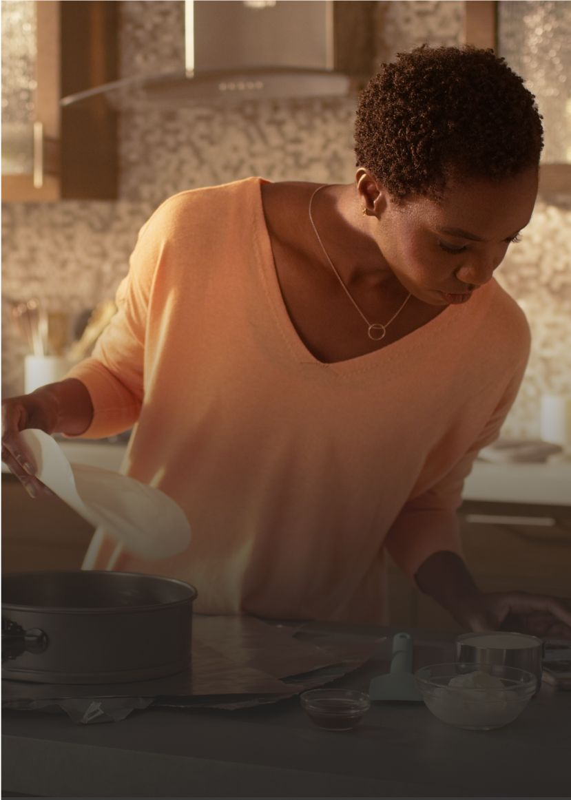 A woman prepares a meal in a kitchen outfitted with Whirlpool® appliances