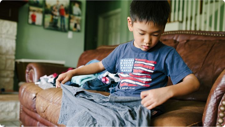 Young boy helping fold laundry on the couch