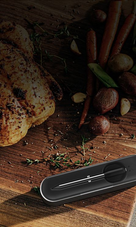 A cooked whole chicken and vegetables next to the Yummly® Smart Thermometer and a phone showing the app