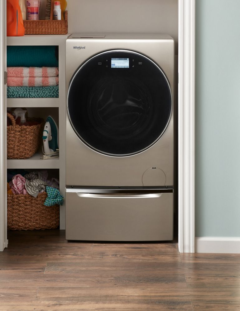 An all-in-one washer/dryer in a laundry closet.