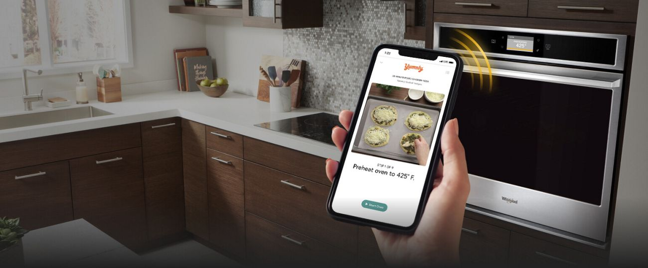 Smartphone sending cooking instructions from the Yummly® app to select Whirlpool® Smart Wall Ovens