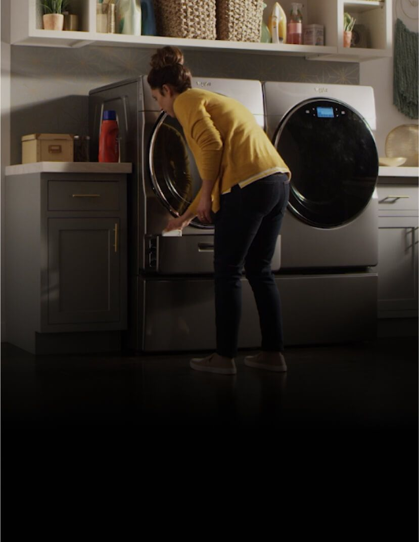 Woman preparing to add detergent to her Whirlpool® washer