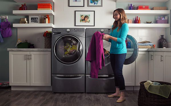 A person getting clothing out of a washer or dryer.