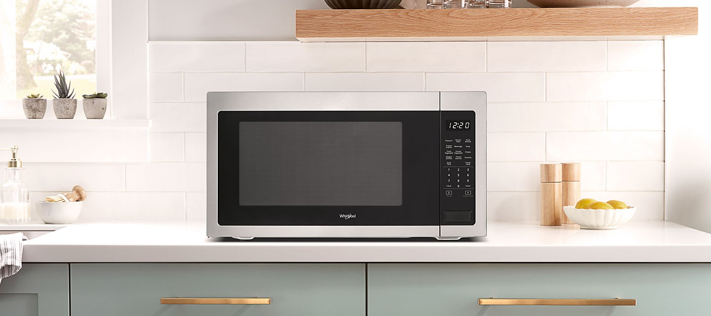 Whirlpool® Countertop Microwave in front of white backsplash