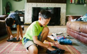 A child folding clean laundry in a living room
