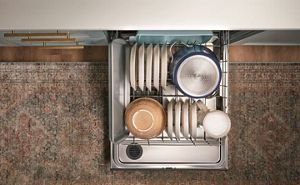 Open Whirlpool® dishwasher showing both racks fully loaded