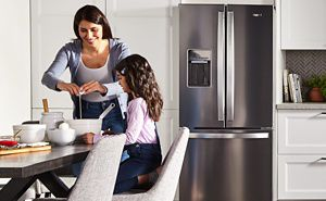 Woman and child cooking on counter in front of a French door refrigerator