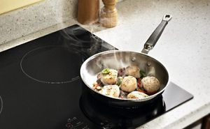 Scallops cooking in a frying pan on a cooktop