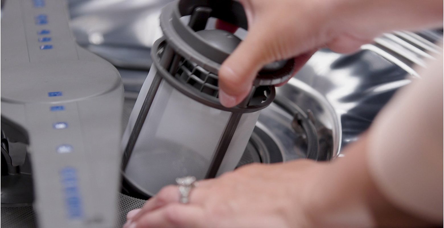 A person removing a filter from a dishwasher