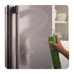 Hand spraying affresh® stainless steel cleaner onto refrigerator