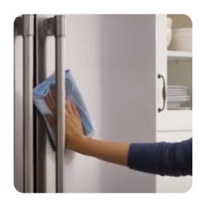 Hand wiping a stainless steel refrigerator with a dry cloth