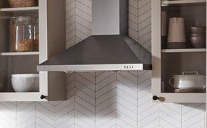 Range hood between white cabinets