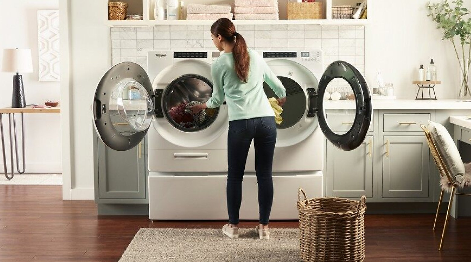 A woman transferring laundry from a front load washer to a front load dryer.